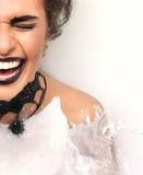 Kvinnaframsidan som skrattar att le i vit, mjölkar buth med färgstänk Arkivfoto