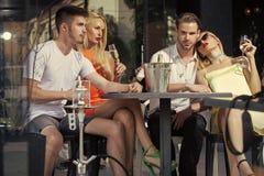 Kvinnaframsidaskönhet kopplar samman kvinnor, och män kopplar av i det utomhus- shishakafét Royaltyfri Bild