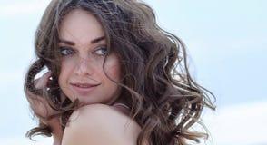 Kvinnaframsidastående på stranden Lycklig härlig lockig-haired flickanärbild, vinden som fladdrar hår Vårstående på beaen Fotografering för Bildbyråer