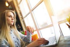 Kvinnafreelancerdrömmar av något avslappnande sammanträde i ett kafé nära ett stort fönster på en tabell med en bärbar dator och  Royaltyfria Bilder