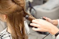 Kvinnafrisör som gör frisyren till den blonda flickan i skönhetsalong royaltyfri foto