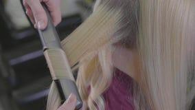 Kvinnafrisördanande krullar på blont hår med krullande järn på skönhetsalongen stock video