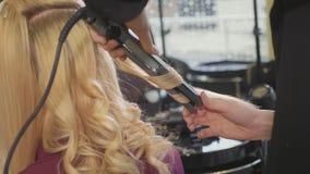 Kvinnafrisördanande krullar på blont hår med krullande järn på skönhetsalongen arkivfilmer