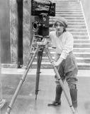 Kvinnafungerande filmkamera (alla visade personer inte är längre uppehälle, och inget gods finns Leverantörgarantier att det ska  Fotografering för Bildbyråer
