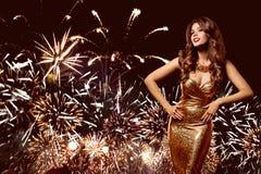 Kvinnafyrverkeriparti, modemodell Celebrating i guld- klänning arkivbilder