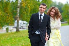 Kvinnagrimaser som rymmer mans hand och går runt om en parkera Fotografering för Bildbyråer