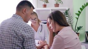 Kvinnahälsa, doktor talar om dåliga resultat av analys till ett upprivet gift par på mottagande i ett kontor lager videofilmer