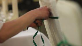 Kvinnahänder dekorerar stolar på en gifta sig ceremoni lager videofilmer
