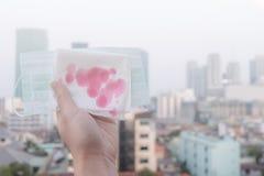 Kvinnahänder eller kvinnliga händer som rymmer en skyddande maskering och en servett med blod på grund av luftförorening i staden royaltyfri foto