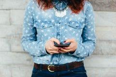 Kvinnahänder genom att använda telefonen Arkivbild