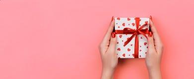 Kvinnahänder ger valentin eller annan ferie handgjord gåva i papper med det röda bandet Närvarande ask, röd hjärtagarnering av gå arkivbild