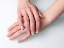 Kvinnahänder med förlovningsringen på vit Arkivbilder