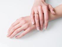 Kvinnahänder med förlovningsringen på vit Royaltyfri Bild