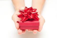 Kvinnahänder med gåva Arkivbilder