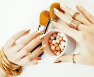 Kvinnahänder med guld- manikyr och många cirklar som rymmer borstar, stilfullt material för makeupkonstnär, rent slut upp rosa fä Arkivfoto