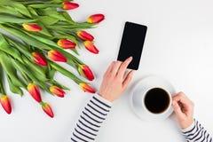 Kvinnahänder med koppen kaffe, mobiltelefonen och härliga blommor samlar ihop på den vita kontorstabellen Royaltyfri Foto