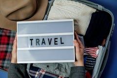 Kvinnahänder med lopp stiger ombord på bakgrunden av Open resväskan Royaltyfria Foton