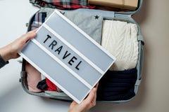 Kvinnahänder med lopp stiger ombord på bakgrunden av Open resväskan Royaltyfria Bilder