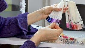 Kvinnahänder med naturlig manikyr och kortslutning spikar att välja Ultraviolet spikar prövkopian från paletten arkivfilmer
