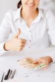 Kvinnahänder med pengar och tummar för euro kontanta upp Arkivbild