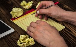 Kvinnahänder och anteckningsbokhandstil på träbakgrund Royaltyfria Foton