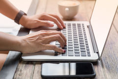 Kvinnahänder på bärbara datorn med mobiltelefonen och kaffe Arkivfoton