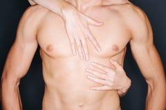 Kvinnahänder på en mans bröstkorg Royaltyfri Bild