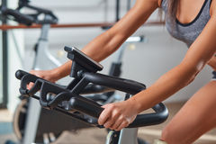 Kvinnahänder på en stationär cykel för stång idrottshallen arkivbilder