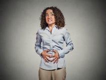 Kvinnahänder på magen som har dåliga knip, smärtar royaltyfria bilder