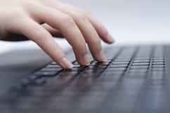 Kvinnahänder på tangentbordet, anteckningsbok Arkivbilder