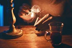 Kvinnahänder som antänder en sista match från en tändsticksask arkivfoto