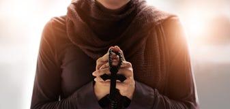 Kvinnahänder som ber med radbandet och arkivbild