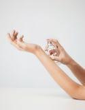 Kvinnahänder som besprutar doft arkivbilder