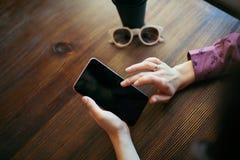 Kvinnahänder som bläddrar skärmen av mobiltelefonen royaltyfria bilder