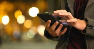 Kvinnahänder som bläddrar telefoninnehållet i natten
