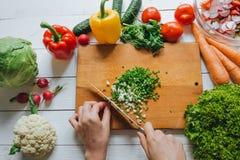 Kvinnahänder som klipper den nya salladslöken på över huvudet bästa sikt för träbräde Vit tabellbakgrund Sunt matlagningbegrepp arkivfoto