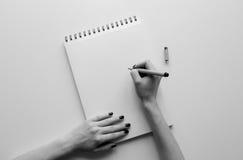 Kvinnahänder som rymmer det pappers- arket eller anteckningsbok och penna Vit tabell arkivbild