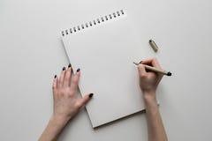 Kvinnahänder som rymmer det pappers- arket eller anteckningsbok och penna Vit tabell royaltyfria foton