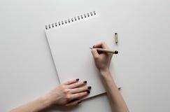 Kvinnahänder som rymmer det pappers- arket eller anteckningsbok och penna Vit tabell royaltyfri foto