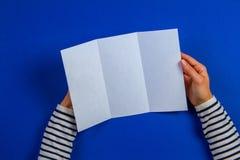 Kvinnahänder som rymmer det tomma vita reklambladbroschyrhäftet Modellarkmall som annonserar häftet på blå bakgrund fotografering för bildbyråer