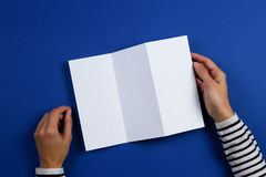 Kvinnahänder som rymmer det tomma vita reklambladbroschyrhäftet Modellarkmall som annonserar häftet på blå bakgrund royaltyfria foton