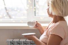 Kvinnahänder som rymmer ett varmt kaffe royaltyfri foto