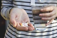 Kvinnahänder som rymmer färgpiller och ett exponeringsglas av vatten band för mått för äpplebegreppshälsa arkivfoto