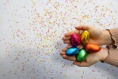 Kvinnahänder som rymmer färgrika chokladeaster ägg med vit bakgrund och färgrika suddiga konfettier arkivbild