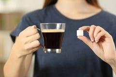 Kvinnahänder som rymmer kaffekoppen och en sockerkub arkivbild