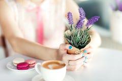 Kvinnahänder som rymmer lavendel Macarons och kopp kaffe royaltyfria bilder