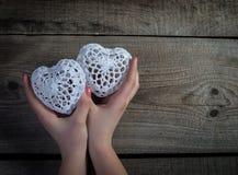 Kvinnahänder som rymmer vit, snör åt hjärtor på gammal wood bakgrund. Fotografering för Bildbyråer