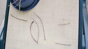Kvinnahänder som skriver ordet FÖRÄLSKELSE med pinnar av träd lager videofilmer