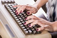 Kvinnahänder som skriver på det gamla datortangentbordet royaltyfri foto