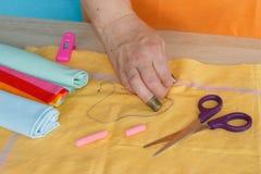 Kvinnahänder som syr den gula klänningen från textilen Royaltyfria Bilder